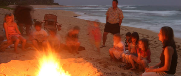 Family singalong at a beach campfire
